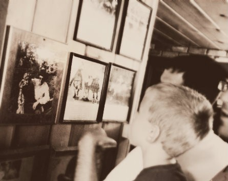 The Cowboy and one of his brothers pointing out to kids, a family photo in one of Wall Drug Store's back hallways..